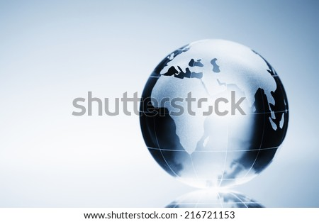 Glass globe on the reflective surface, with copy space. - stock photo