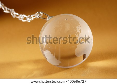 Glass globe with metal chain on yellow background - stock photo