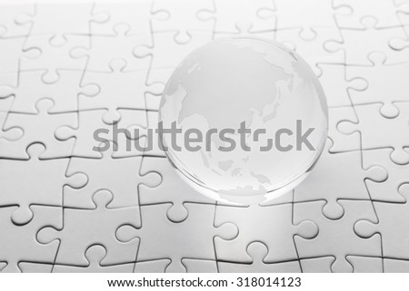 glass globe with puzzle background  - stock photo