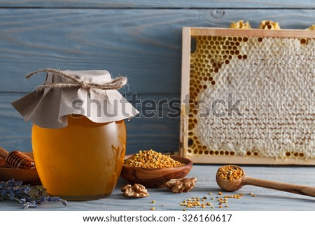 Glass honey jar with bee pollen, honeycombs and lavender on a blue wooden table. - stock photo