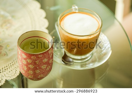 Glass hot coffee cup with white foam surface - stock photo