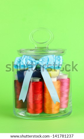 Glass jar containing various colored thread on green background - stock photo