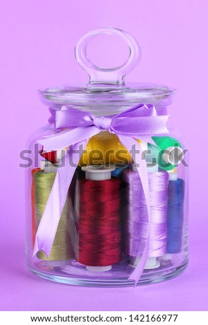 Glass jar containing various colored thread on lilac background - stock photo