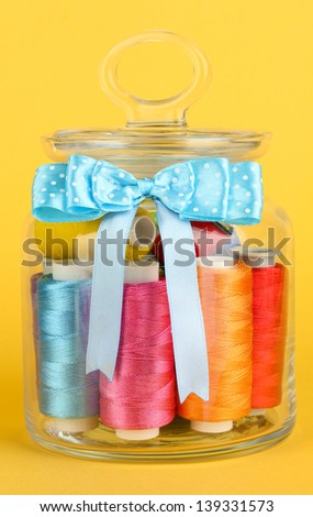 Glass jar containing various colored thread on yellow background - stock photo