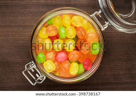 glass jar full of colorful sweets on the wooden table - stock photo