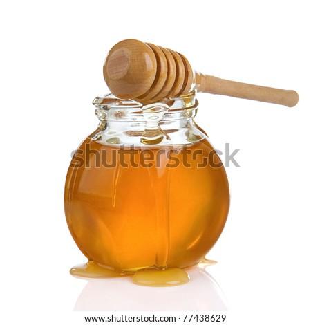 glass jar full of honey and stick isolated on white background - stock photo