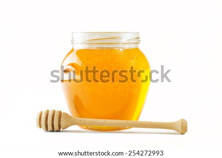 Glass jar full of honey wooden honey dipper - stock photo