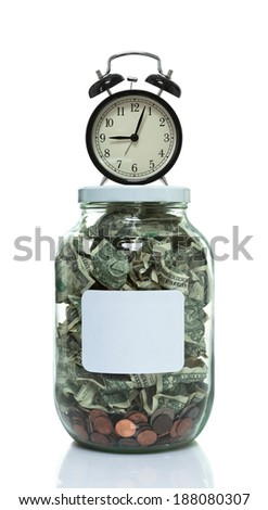 Glass jar full of money with a clock sitting on top - stock photo
