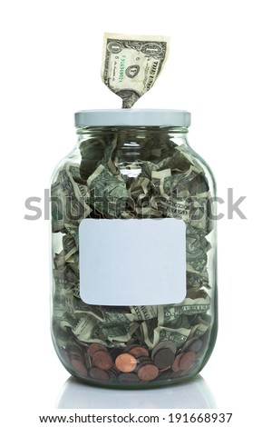Glass jar full of money with a dollar bill in the top - stock photo