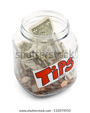 Glass Jar half full of money with a tips label on it, isolated on a white background with drop shadow. - stock photo