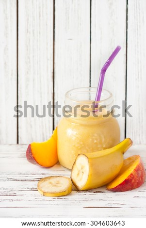 Glass jar of fresh homemade smoothie with banana and peach. - stock photo