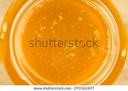 glass jar of fresh honey on wooden background, top view - stock photo