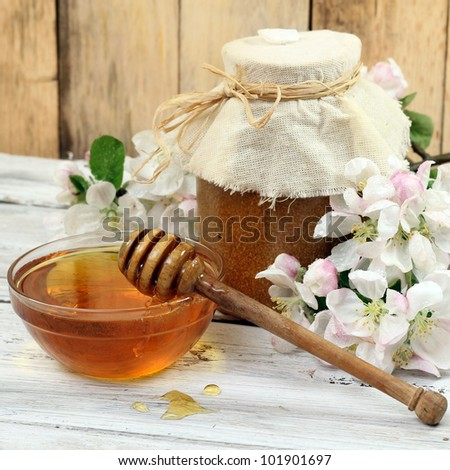 glass jar of honey and stick on wood background - stock photo