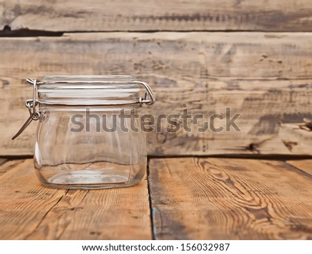 glass jar on old wooden table - stock photo