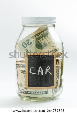 Glass jar on white background with black chalk label or panel and used for saving of US dollar bills for car expenses - stock photo