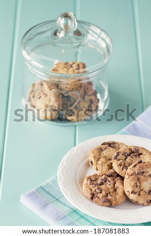 Glass jar with chocolate chip cookies and a plate with cookies on a robin egg blue wooden table. Vintage look. - stock photo