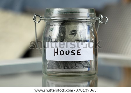 Glass jar with dollar banknotes for house on a table - stock photo