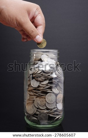 Glass jar with hand hold coin isolated on black background             - stock photo
