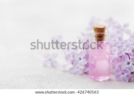 Glass jar with rose water and lilac flowers for spa and aromatherapy, copy space for text - stock photo