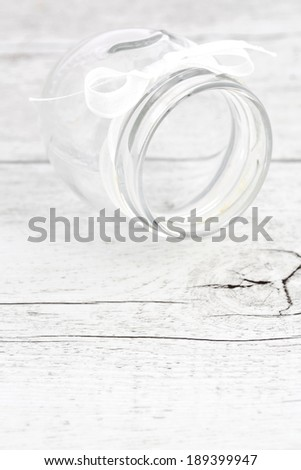 Glass jar with white bow isolated on wooden background - stock photo
