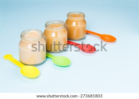 Glass jars of baby food with colorful spoons on blue background - stock photo