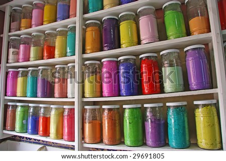 Glass jars of traditional dye powder, in Moroccan market - stock photo