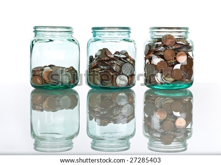 Glass jars with coins on reflective surface, isolated - savings concept - stock photo