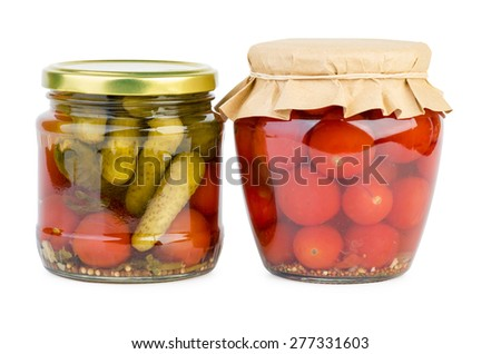 Glass jars with home-mad pickled tomatoes and cucumbers - stock photo