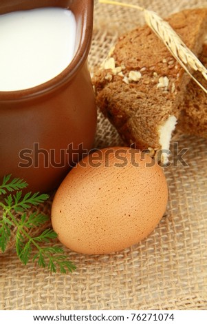 Glass jug with milk and  eggs on natural background of rustic style - stock photo