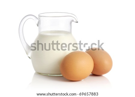 Glass jug with milk and two eggs on white background - stock photo