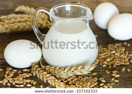 Glass jug with milk, wheat seeds and eggs - stock photo