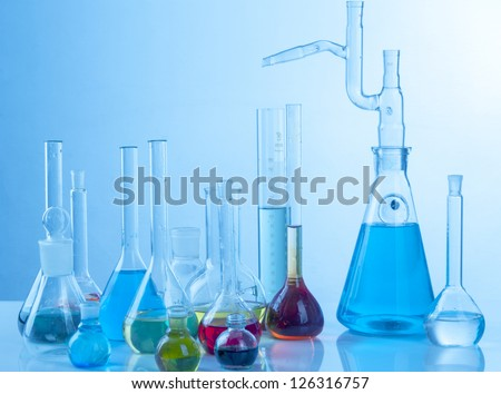 Glass laboratory equipment on blue background - stock photo