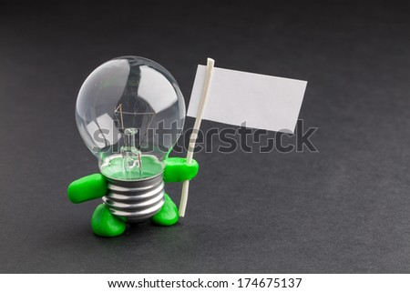 Glass lamp on a black background with green hands and feet holding a blank poster, with space for text.. Concept. Cool and funny. Concept. - stock photo