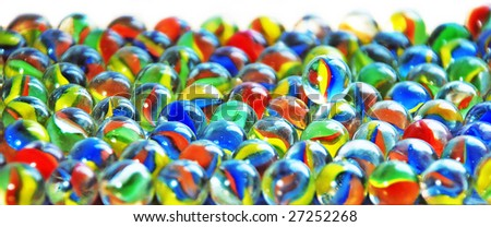 Glass marbles, densely lyings alongside, one marble lies on them from above - stock photo