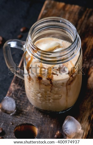 Glass mason jar of ice coffee with ice cream and chocolate sauce, served with coffee beans and ice cubes on wooden chopping board over black textured background. - stock photo