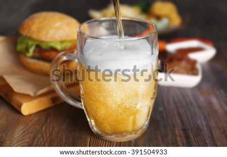 Glass mug of draft light beer with snacks on dark wooden table, close up - stock photo