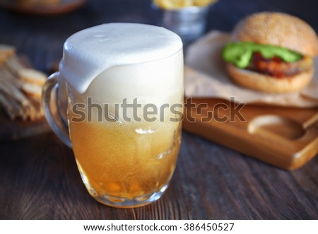 Glass mug of light beer with hamburger on dark wooden table, close up - stock photo