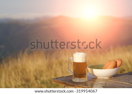 Glass mug with lager or porter tasty frothy beer and plate of sausage on wooden table top sunny day outdoor on natural with mountain hills and yellow dry grass background with flash light, horizontal - stock photo