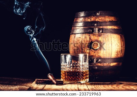 Glass of alcohol and smoking noble cigar on a black background - stock photo