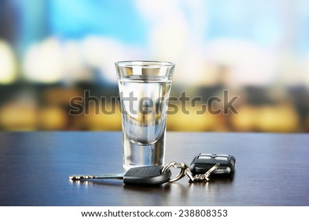 Glass of alcoholic drink and car key, on wooden table, on light background - stock photo