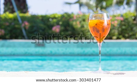 Glass of Aperol Spritz cocktail on the pool nosing at the tropical resort. Horizontal, wide screen, cocktail on right side - stock photo