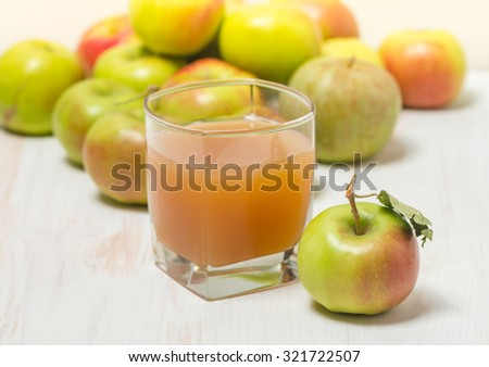 Glass of apple juice and green apples on white wooden background - stock photo