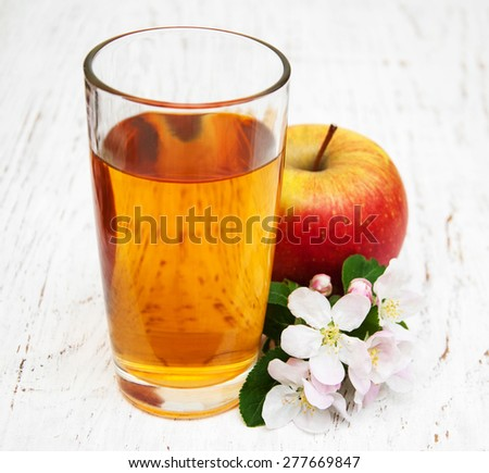 glass of apple juice with apples and flowers on a wooden background - stock photo