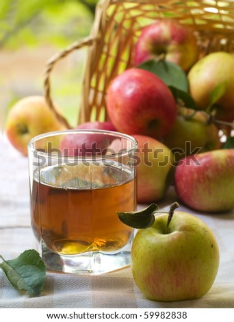 Glass of apple juice with basket of apple in background - stock photo