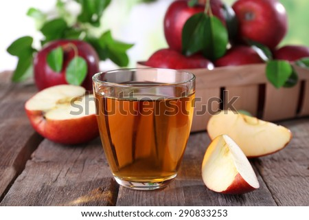 Glass of apple juice with red apples on wooden table, closeup - stock photo