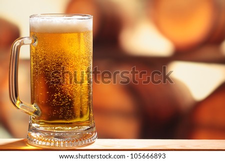 Glass of beer against barrels - stock photo