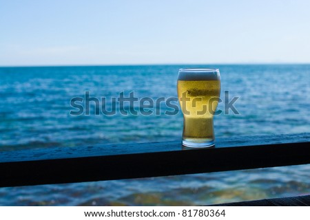 Glass of beer against sea - stock photo
