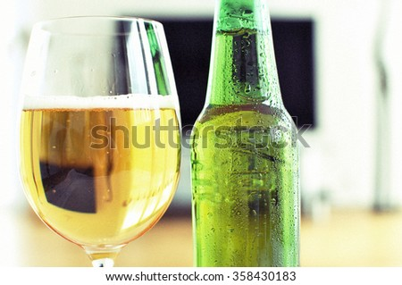 Glass of beer against TV-set - stock photo