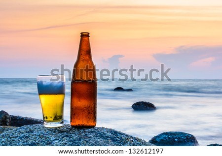 Glass of beer and a bottle on the rock at sea - stock photo