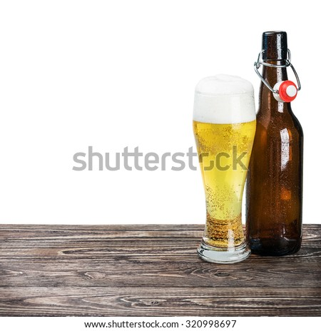glass of beer and an empty bottle on the table isolated on white background - stock photo